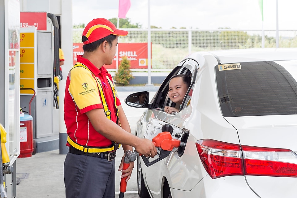 pump attendant filling the car with petrol nozzle